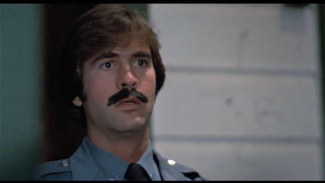 A police officer is shocked and horrified after witnessing the aftermath of the Judy Curling Iron Massacre. It was so disturbing  his mustache transformed into sculpting putty.