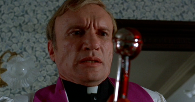 The worst cinematic priest ever mourns the blood ejaculated by the cyborg cock of Jesus.
